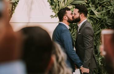 men-wearing-suit-kissing-in-front-of-people-3491999-scaled.jpg